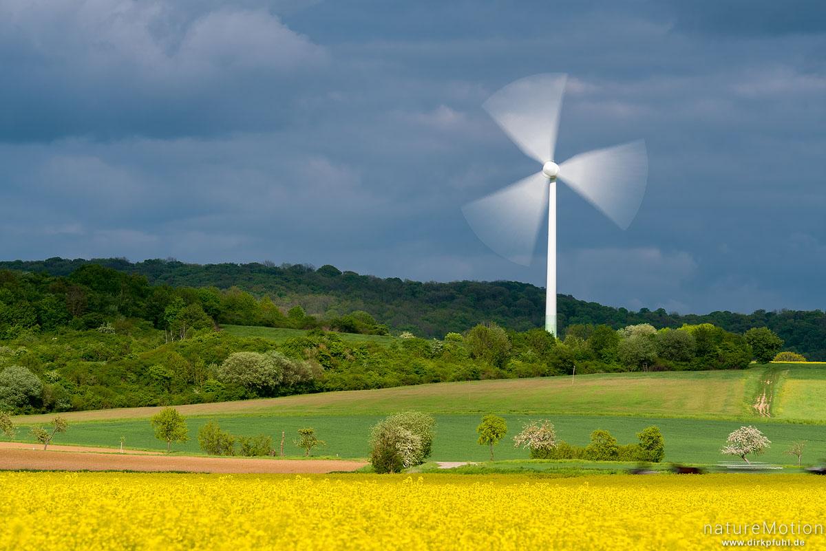Windrad, verwischter Rotor, blühendes Rapsfeld, Feldmark südlich von Göttungen, Göttingen, Deutschland