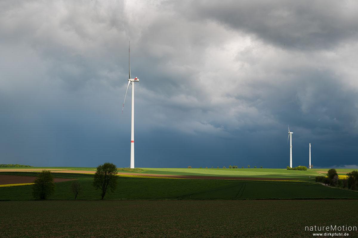 Windräder inmitten von Ackerflächen, Regenwolken, Landolfshausen im Eichsfeld, Deutschland